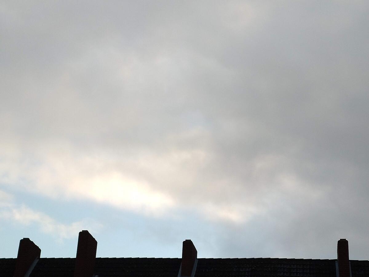 Dunkelgrau bewölkter Himmel über einem Dachfirst, über dem ein hellblauer Streifen steht