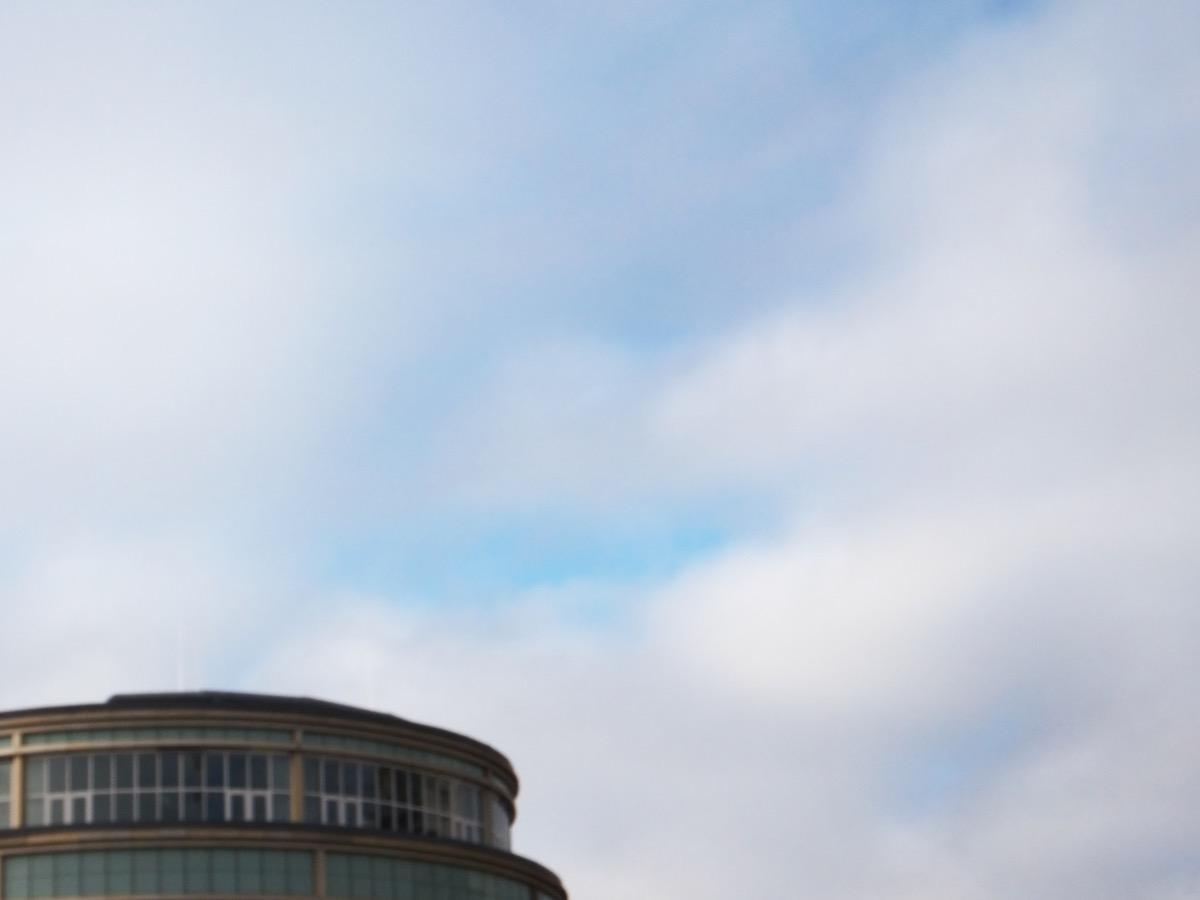 Wolken und etwas blauer Himmel, unten ein Gebäude-Teil