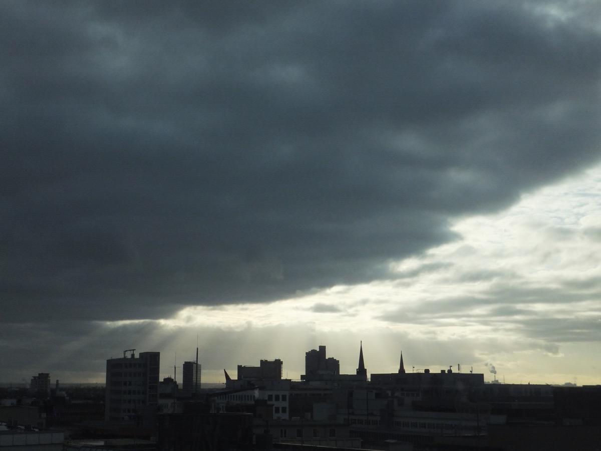 schwarzblaue Wolkendecke über der Kölner Oper, die Sonne bricht durch