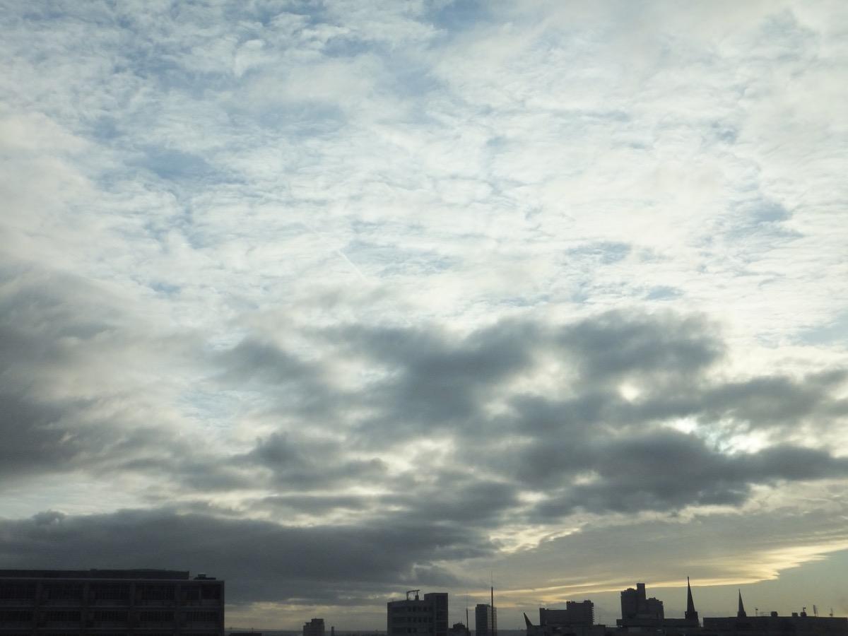 Wolkendecke über der Kölner Oper, der Himmel kommt etwas blau durch
