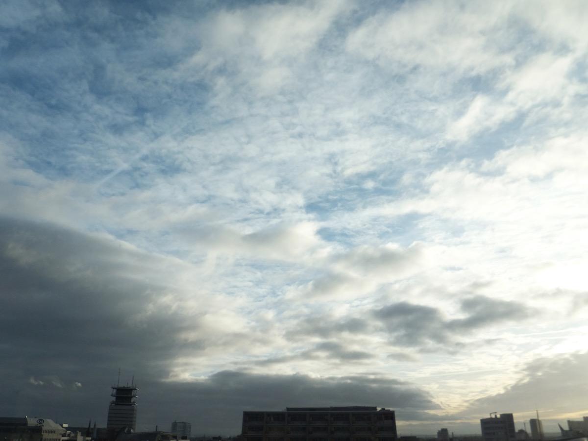 dunkle Wolkendecke über der Kölner Oper zieht ab, Federwolken am blauen Himmel