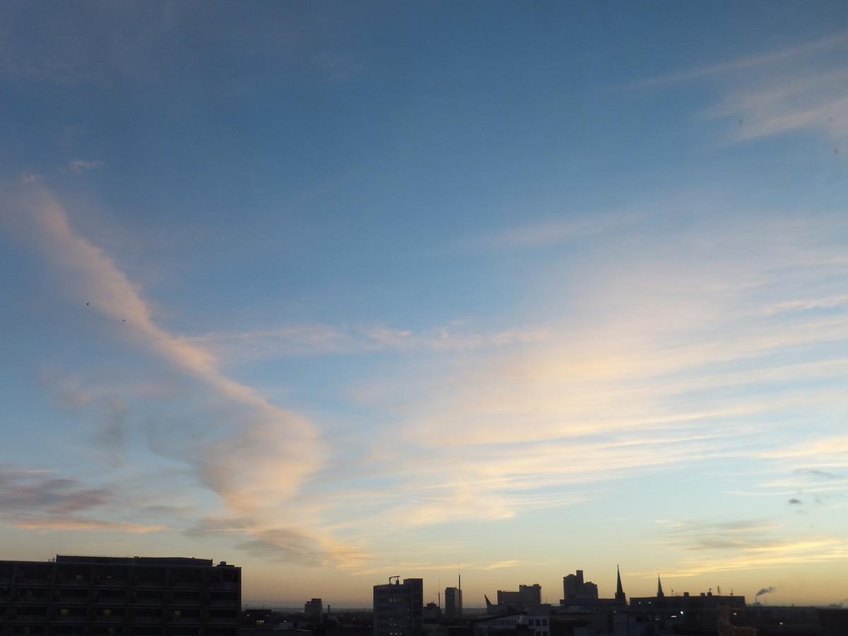 noch vereinzelte Wolken über der Kölner Oper, blauer Himmel mit ausgeprägten Federwolken, leicht goldenes Abendlicht