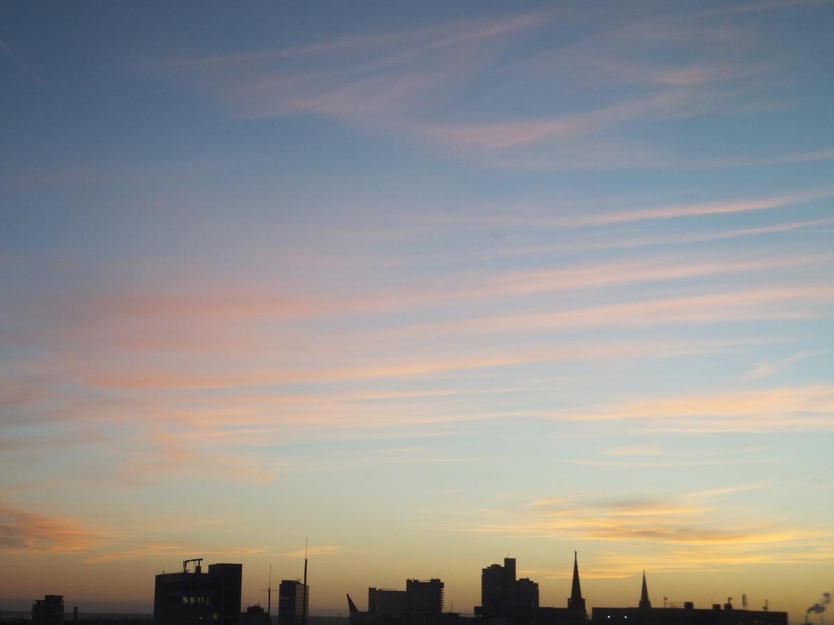 noch vereinzelte Wolken über der Kölner Oper, blauer Himmel mit ausgeprägten Federwolken, rot-goldenes Abendlicht