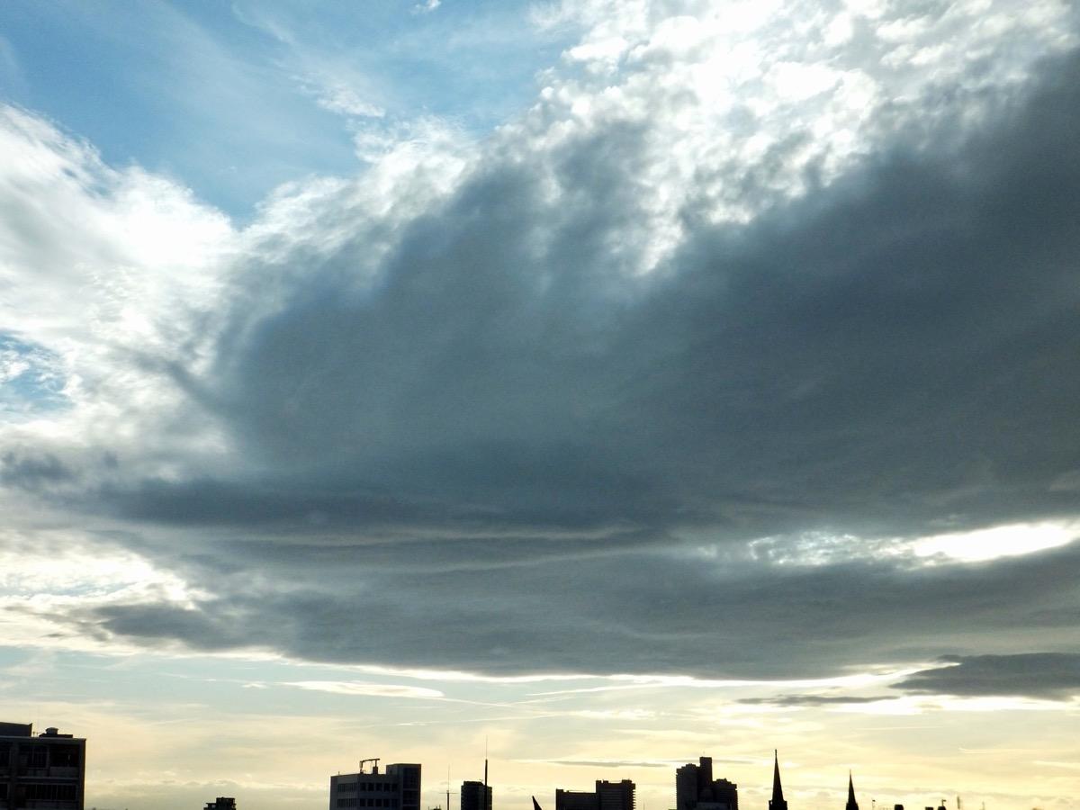 Sehr große dunkle Wolke, darüber blauer Himmel, darunter schon leicht goldenes Abendlicht.
