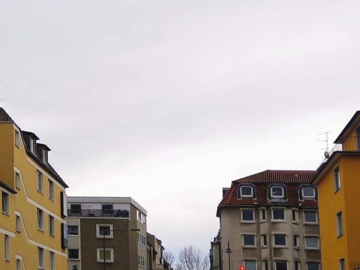 Dunkelgrau-weiß-blau abgestufter Himmel, im Vordergrund Häuser