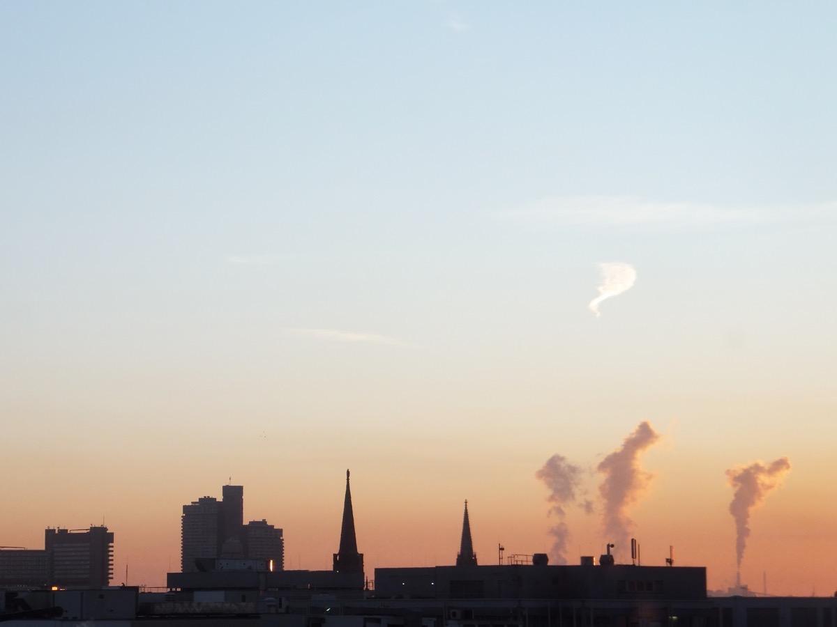 Drsi Wasserdampf-Wolken steigen im Abendlicht über der Silhouette Kölns auf