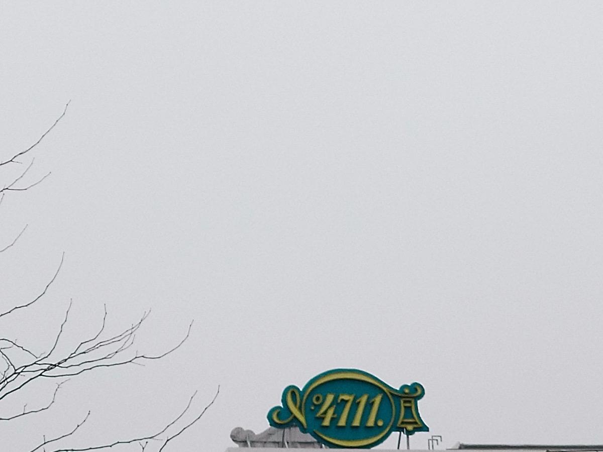 Ein komplett grauer Himmel über dem Firmenschild von 4711