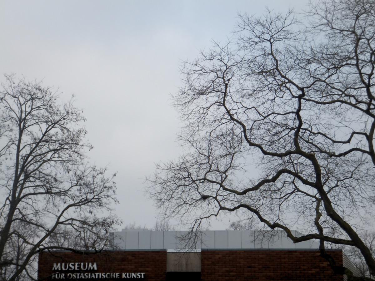 grau-weiße Wolken vor blaßblauem Himmel, im Vordergrun blattlose Bäume und das Kölner Museum für Ostasiatische Kunst