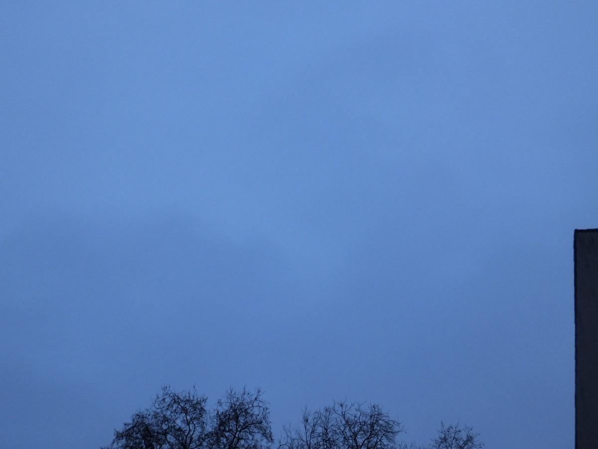 Abendlich dunkelblauer Himmel mit ein paar dünnen Wolken, unten eine unbelaubte Baumkrone, rechts eine Hauswand
