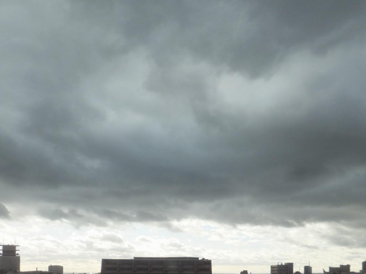 Dunkelgraue Wolkendecke, am Horizont Licht und Cumulus