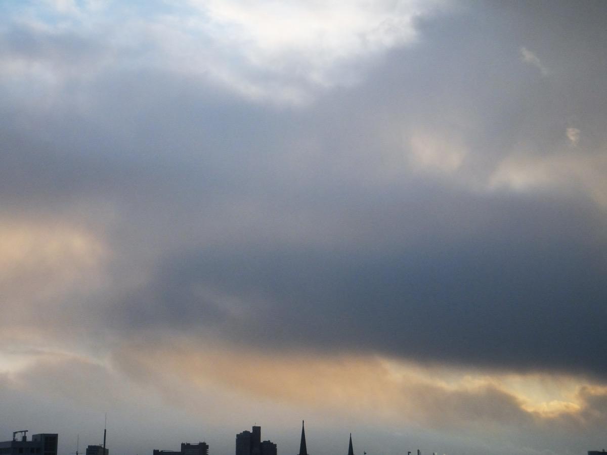 Dunkelgraue Wolkendecke, eine durch das Sonnenlicht gelblich gefärbte Wolke regnet ab