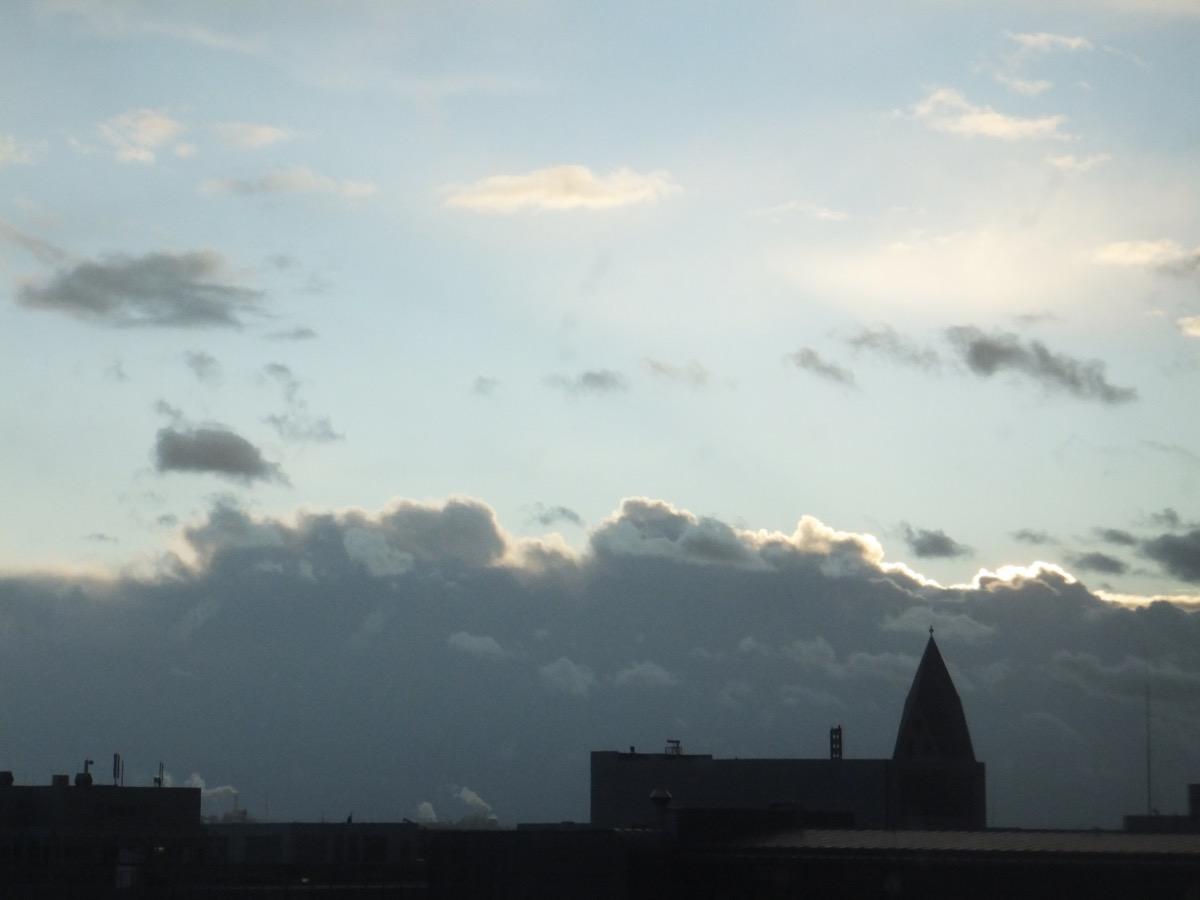 wird von hinten durch die Sonne beleuchtet; im Vordergrund Häuserzeilen und eine Kirche
