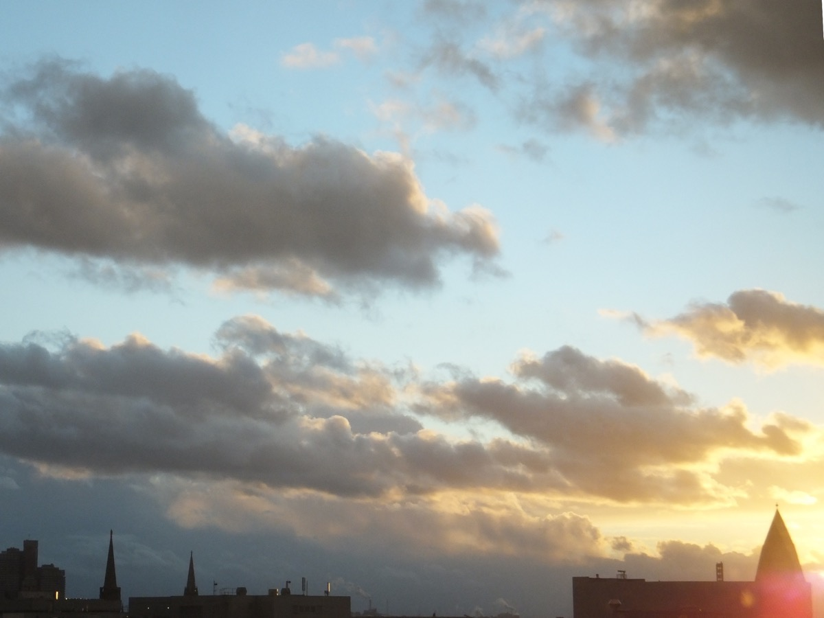 Wolkenmassen vor blauem Abendhimmel werden vom Abendlicht vergoldet