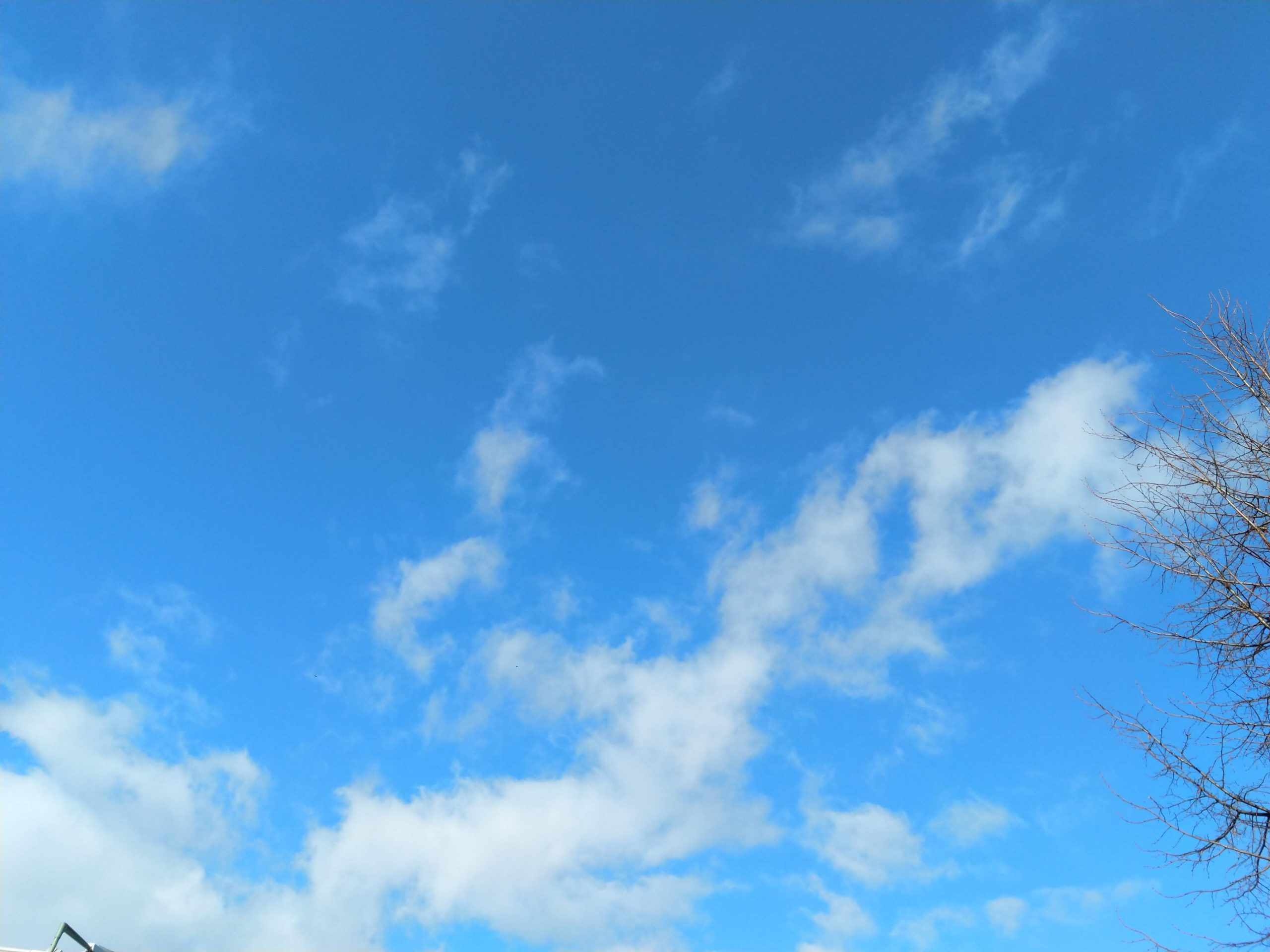 Kleine weiße Federwolken am hellblauen Himmel