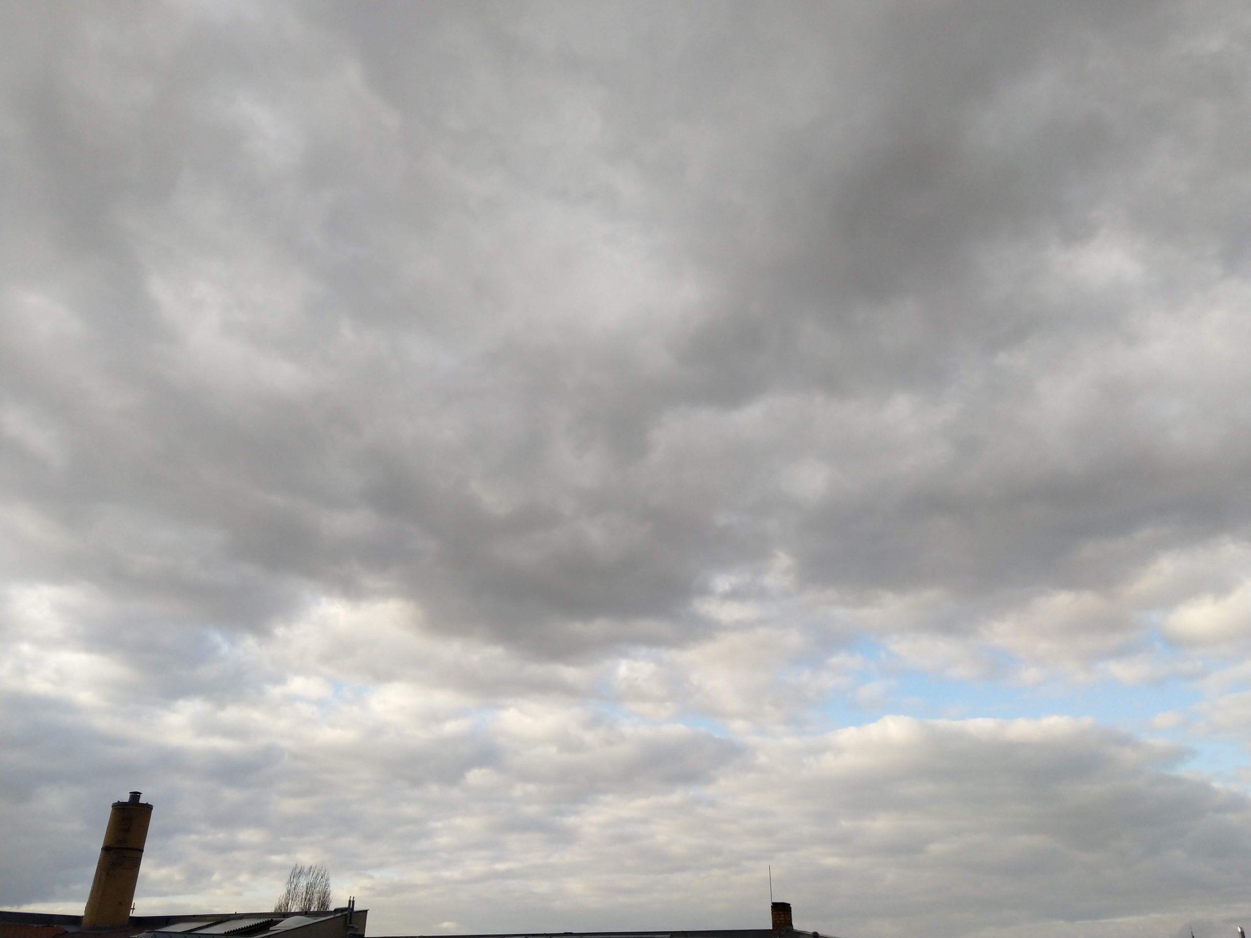 Dunkle Regenwolken, nur ein kleiner Fleck blauer Himmel