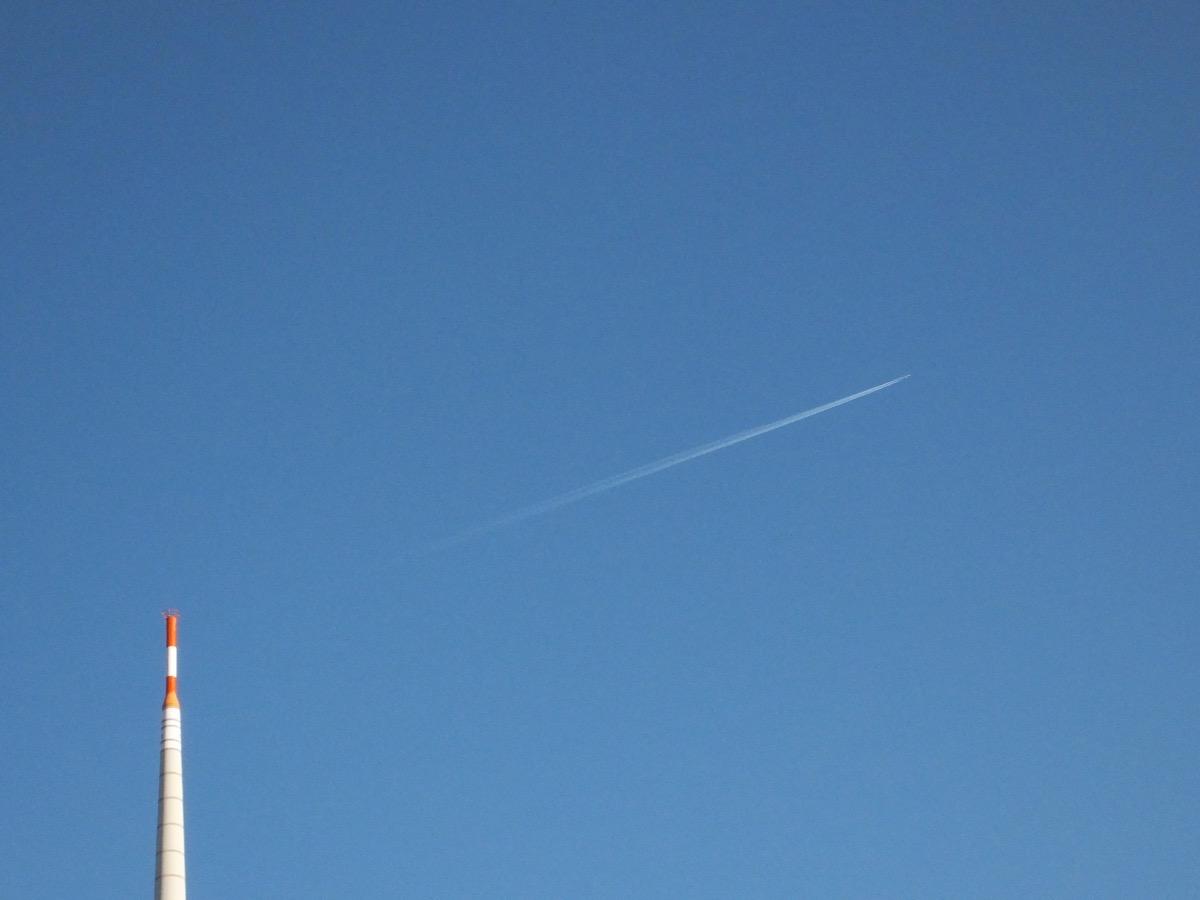 Ein wolkenloser blauer Himmel mit einem Kondensstreifen eines Flugzeugs, links unten die Spitze eines Fernsehturms