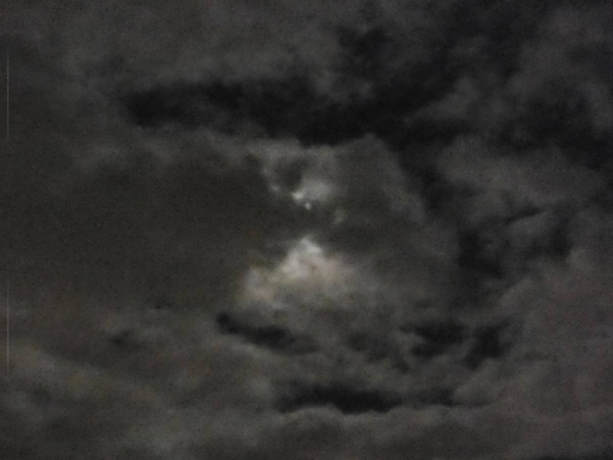 Dunkle Wolken nachts vor Vollmond