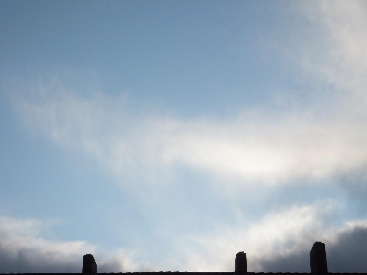 Dünne Schleier- und ein kleiner Streifen Regenwolken vor hellblauem Himmel