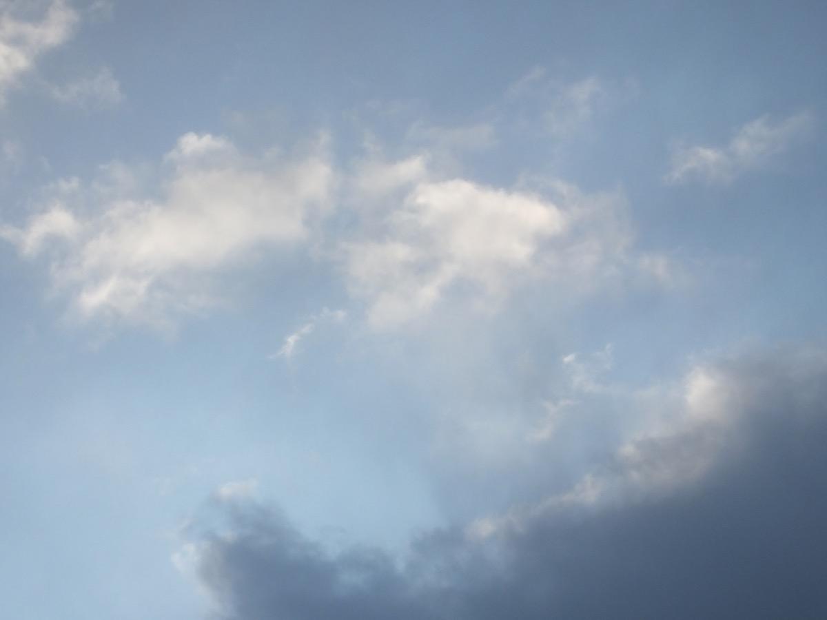 Eine dunkle und eine kleine weiße gezupfte Wolken am hellblauen Himmel