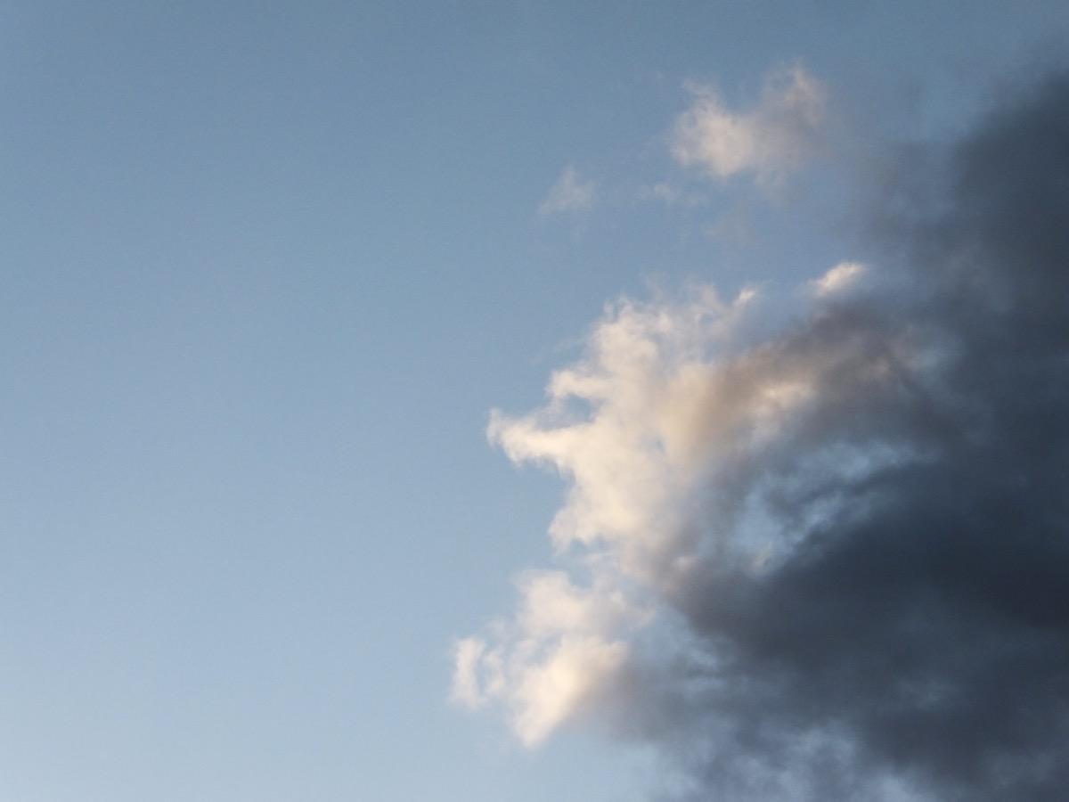 Eine helle, beleuchtete Wolke neben einer dunklen vor hellblauem Himmel