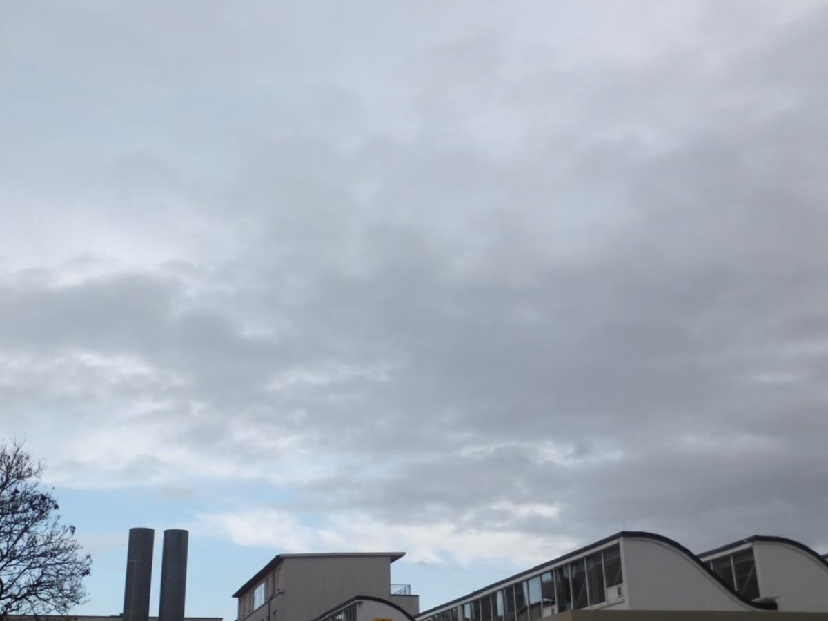 Graue und helle Wolken, unten ein hellblauer Streifen Himmel und ein Fabrikdach in Wellenform