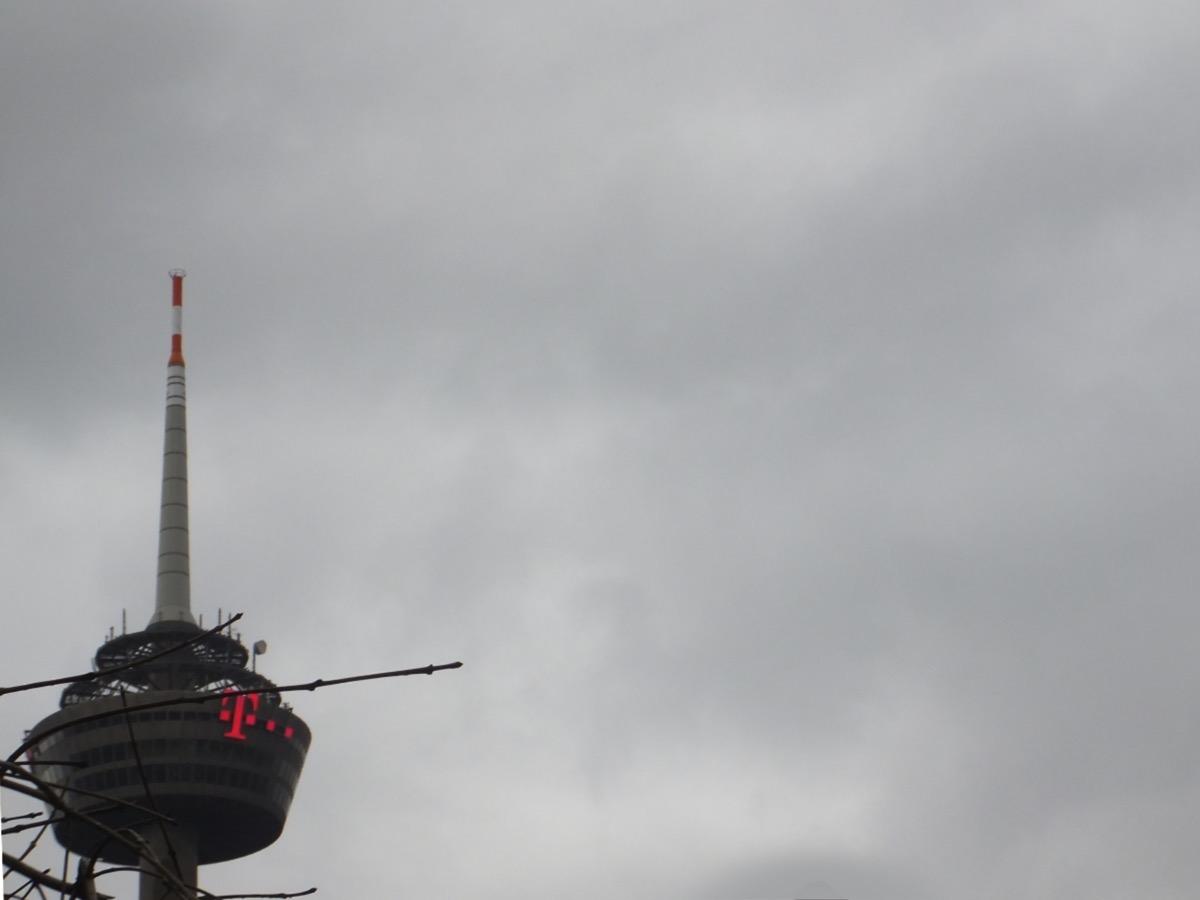 Eine dunkelgraue Wolkendecke, im Vordergrund links der dunkelgraue Kölner Fernsehturm