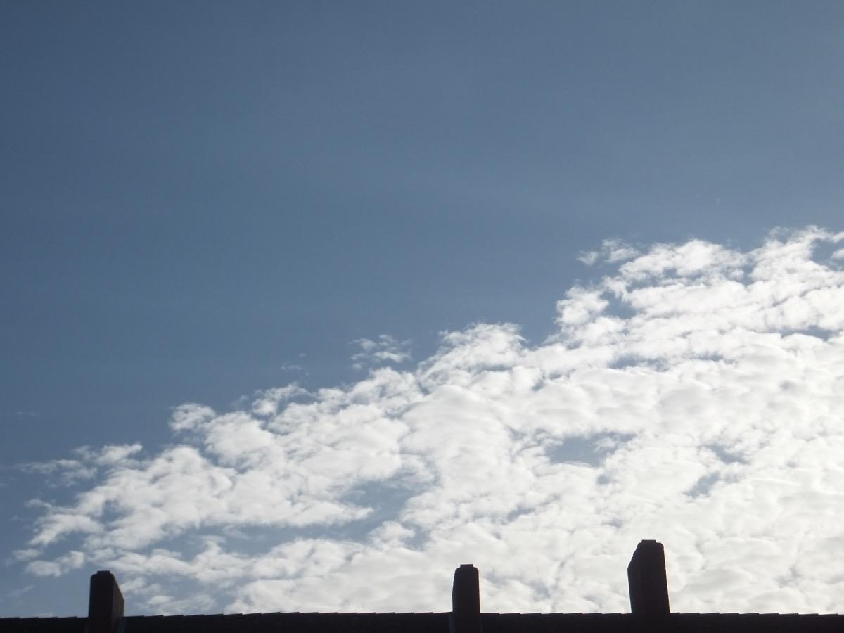 Weiße Schäfchen-Wolken vor blauem Himmel