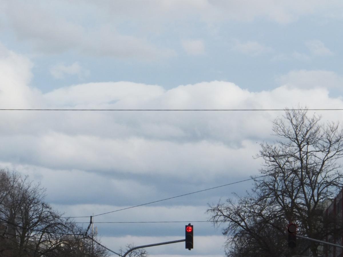 dicke Wolkenstreifen an hellblauem Himmel, unten Leitungen, Baumkronen und eine rote Ampel
