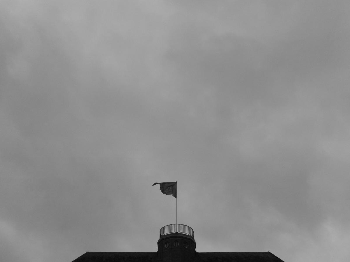 Dunkelgraue Wolken, im Vordergrund unten ein Hausdach mit einer Fahne