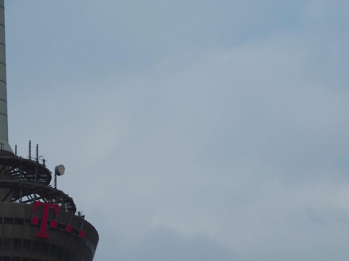 Blasse Wolken vor blassblauem Himmel, links im Vordergrund ein Teil des Kölner Fernsehturms