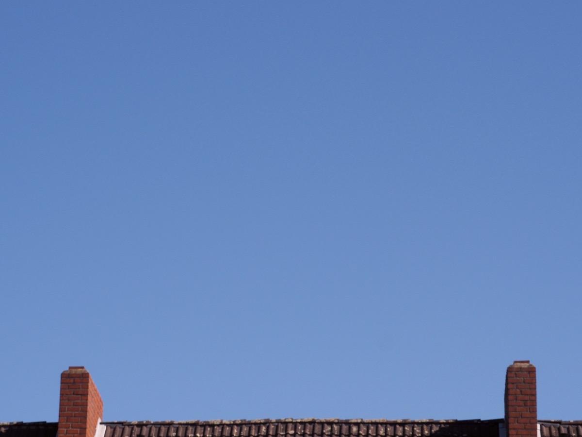 Ein wolkenloser blauer Himmel, unten ein Dach und zwei Schornsteine