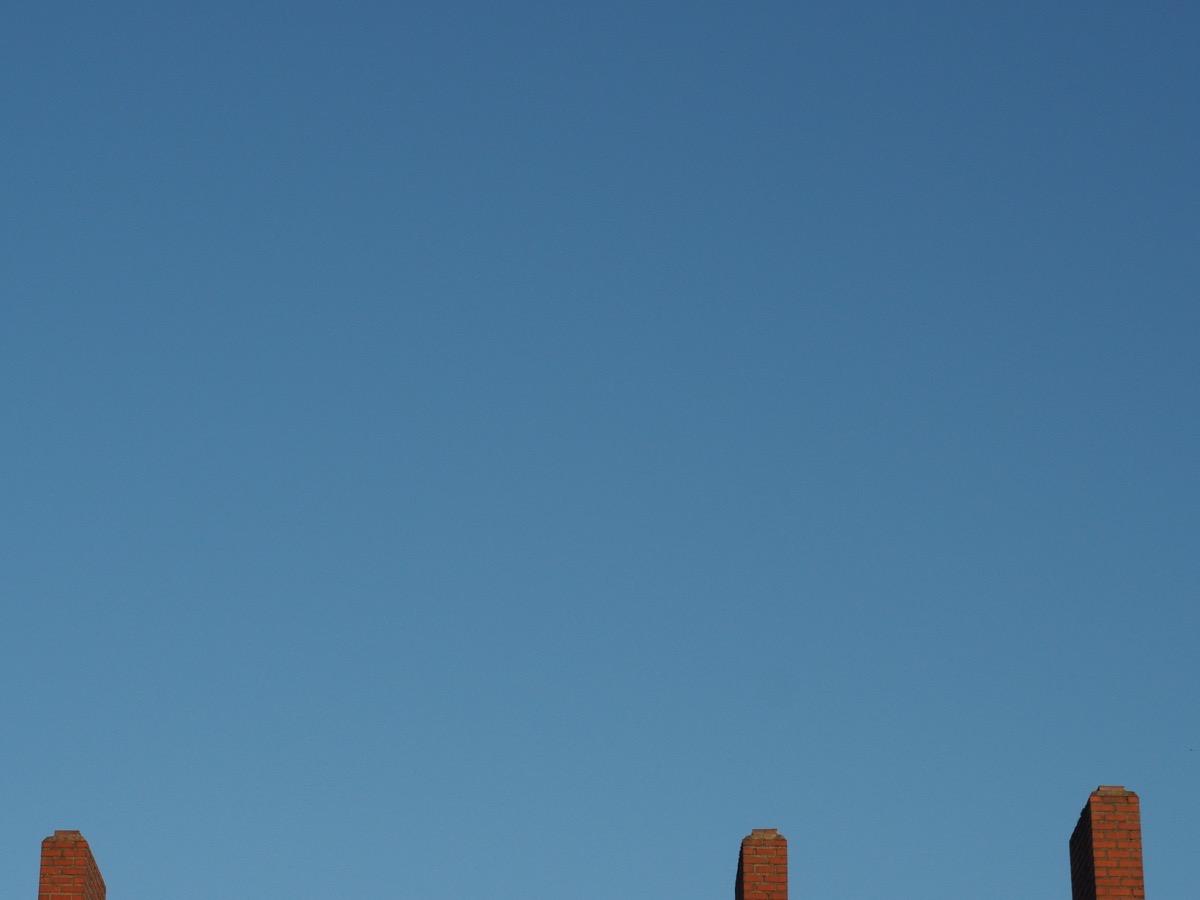 Ein wolkenloser blauer Himmel, unten ein Dach und drei Schornsteine