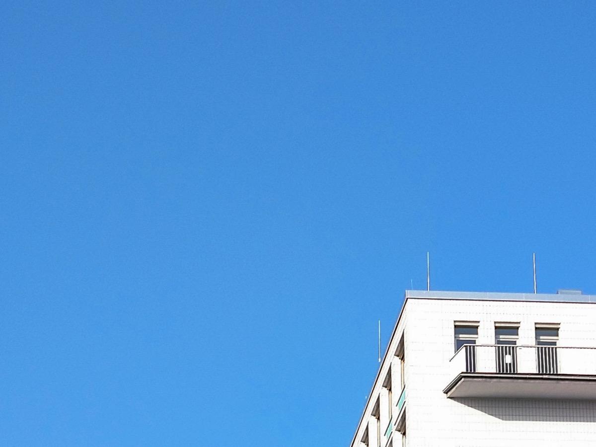 Ein Teil eines weißen Gebäudes mit Balkon vor blauem Himmel