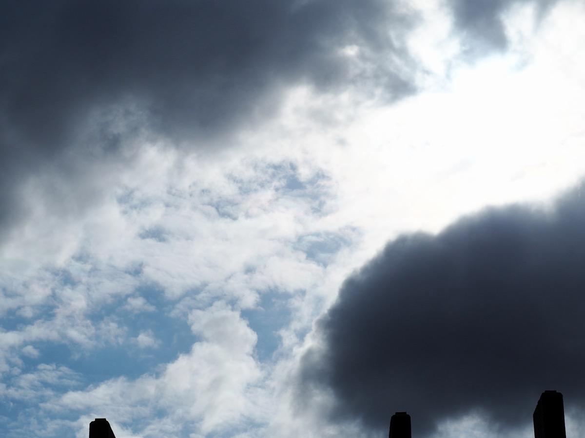 Dunkel und weiße Wolken vor hellblauem Himmel