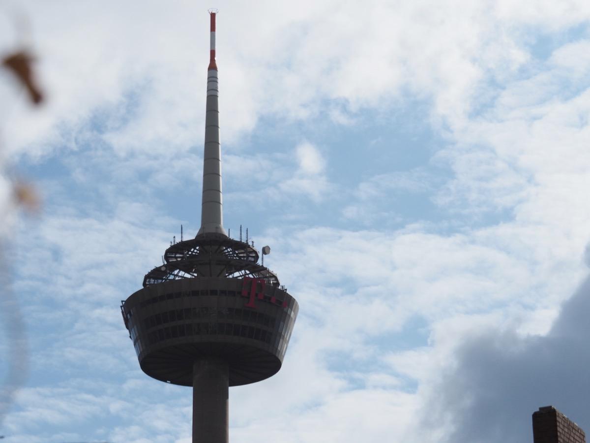 Weiße Federwolken am hellblauen Himmel, im Vordergrund der Kölner Fernsehturm