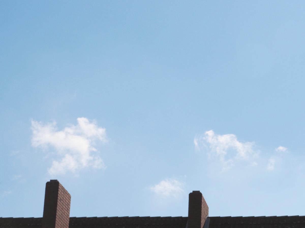 Zwei kleine Wolkenfetzen am hellblauen Himmel, unten ein Dachfirst und zwei Schornsteine