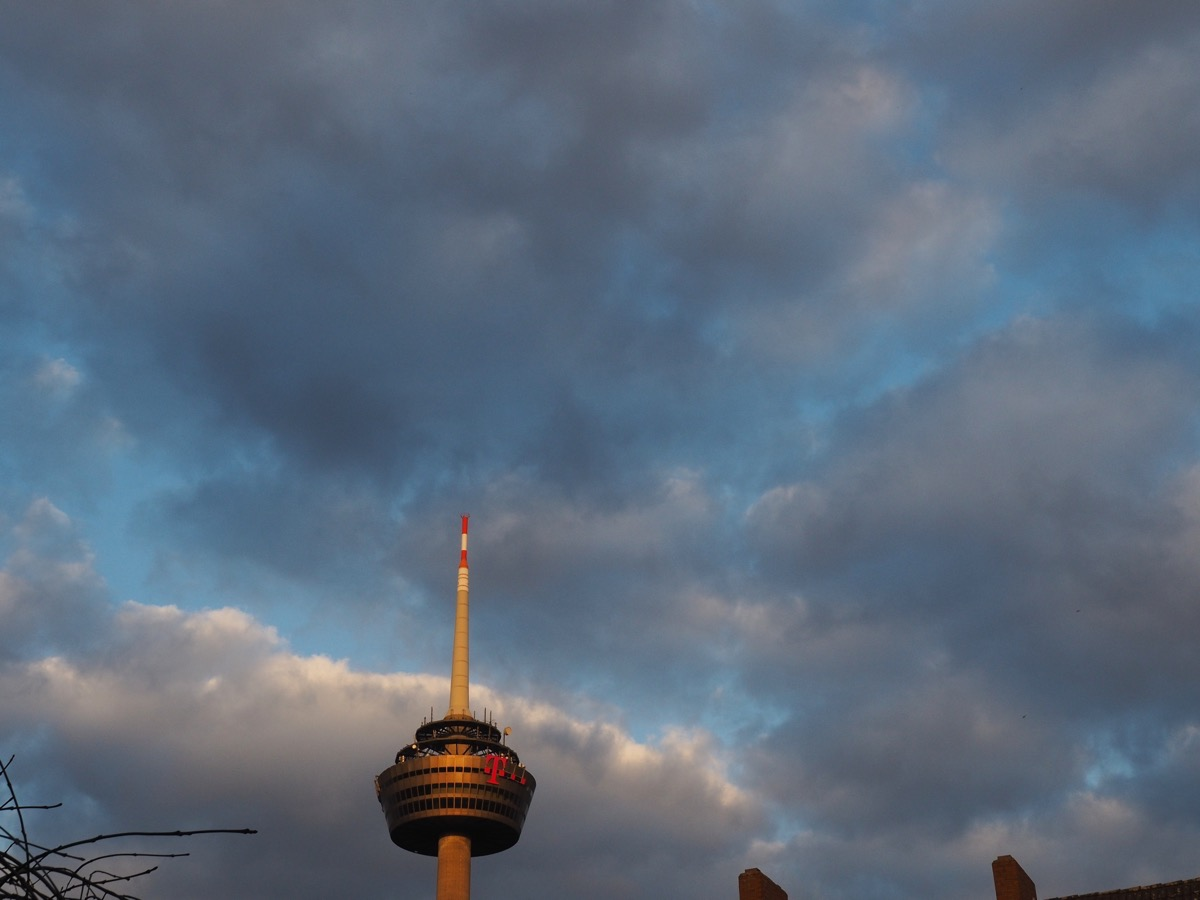 Grauen und weiße Wolken vor blauem Himmel, im Vordergrund der Kölner Fernsehturm