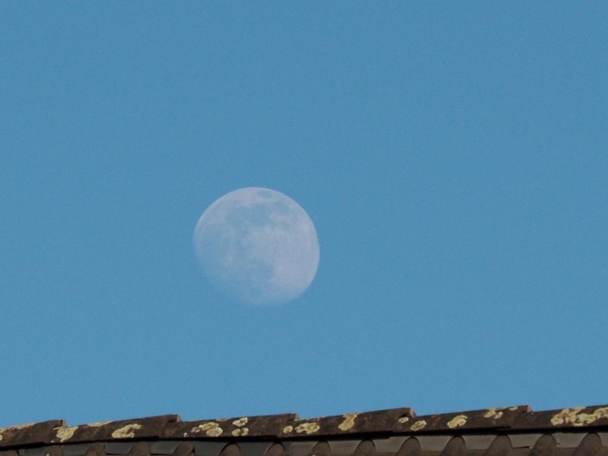 Ein sehr voller Mond über einem Dachfirst am blauen Himmel